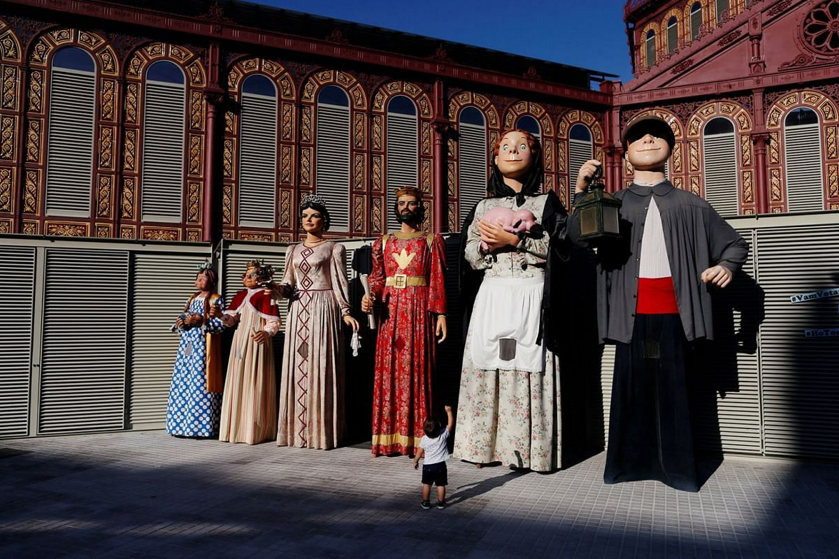 A child gestures next to Catalan traditional giants as he takes part in the activities of the Sant Antoni neighborhood on Sept 30, 2018,. to commemorate the first anniversary of the banned independence referendum in the region on October 1, 2017, in