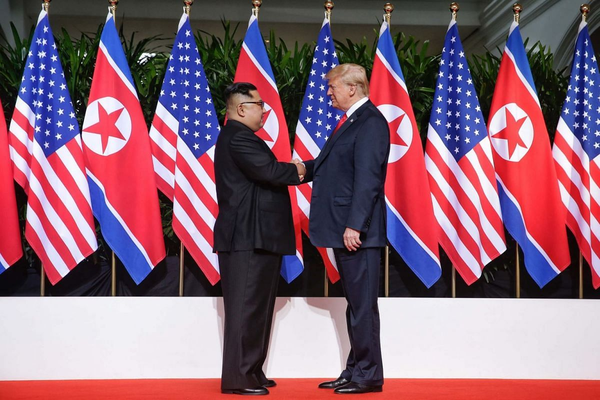 US President Donald Trump and North Korean leader Kim Jong Un shaking hands for the first time at the start of their historic meeting at  Capella Singapore, on June 12, 2018.