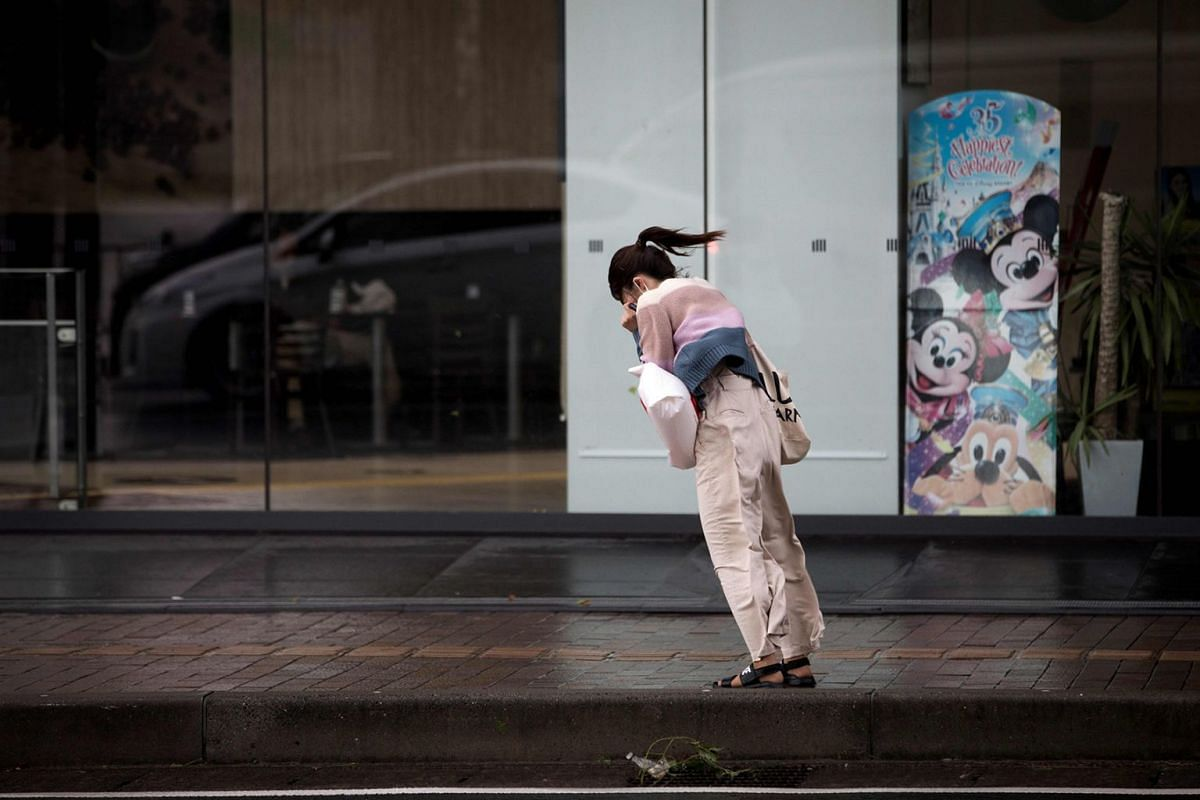 A woman walks against the strong winds after Typhoon Trami hit the city of Kagoshima on Kyushu island on September 30, 2018. The powerful typhoon hurtled toward Japan's mainland after injuring dozens on southern islands, as weather officials warned t
