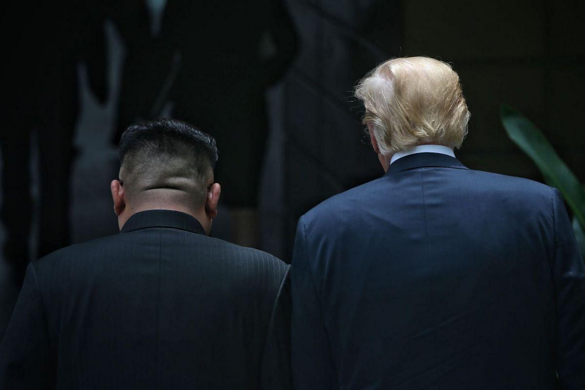US President Donald Trump and North Korean leader Kim Jong Un walk shoulder to shoulder at their historic meeting at Capella Singapore, on June 12, 2018.