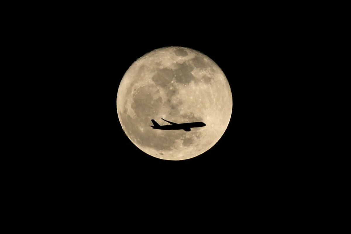 A passenger plane flying above Changi Business Park was dwarfed by the moon, on Oct 6, 2017, a day after harvest moon.