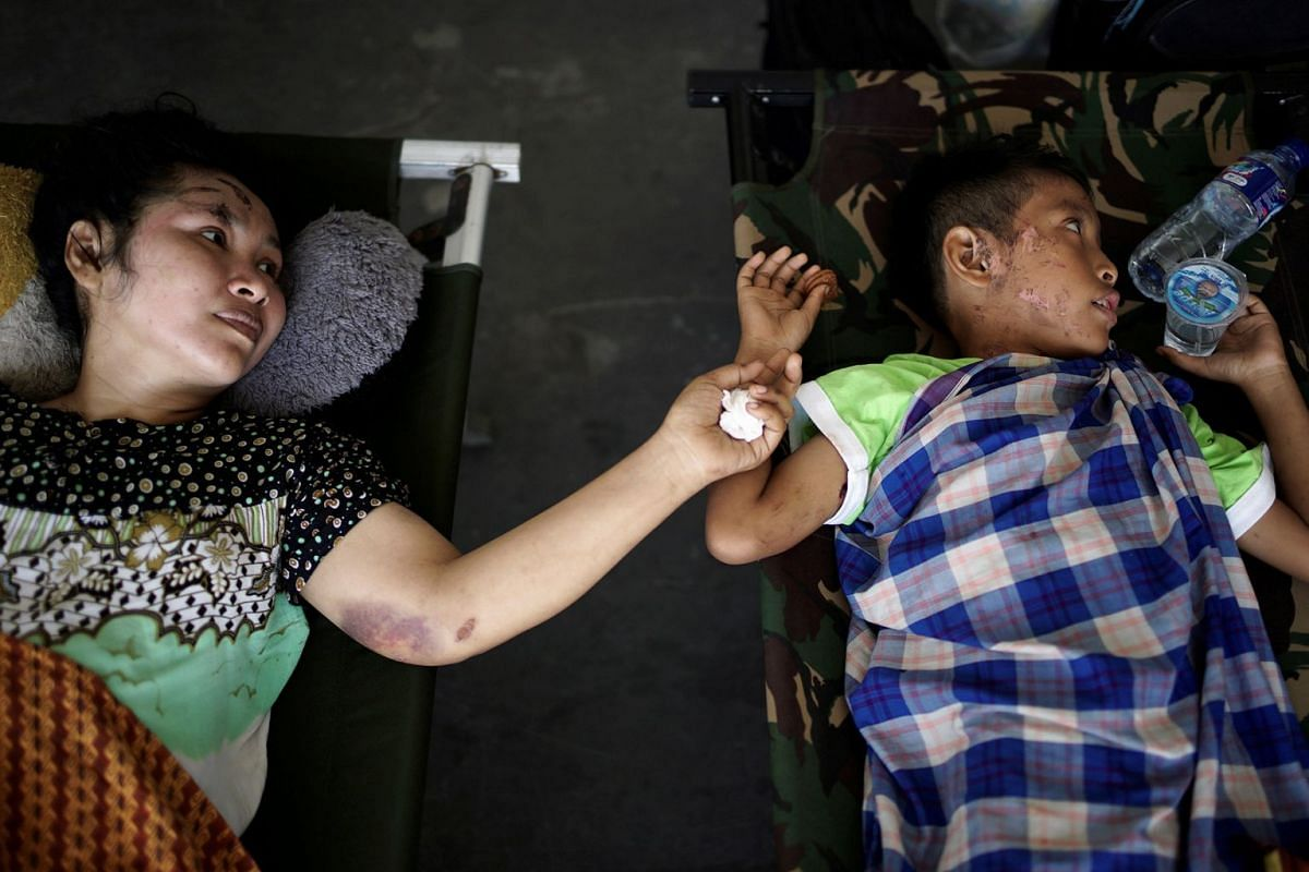 A mother and her son, both injured by the earthquake and tsunami, wait to be airlifted out by a military plane at Mutiara Sis Al Jufri Airport in Palu, Central Sulawesi, Indonesia, October 3, 2018.