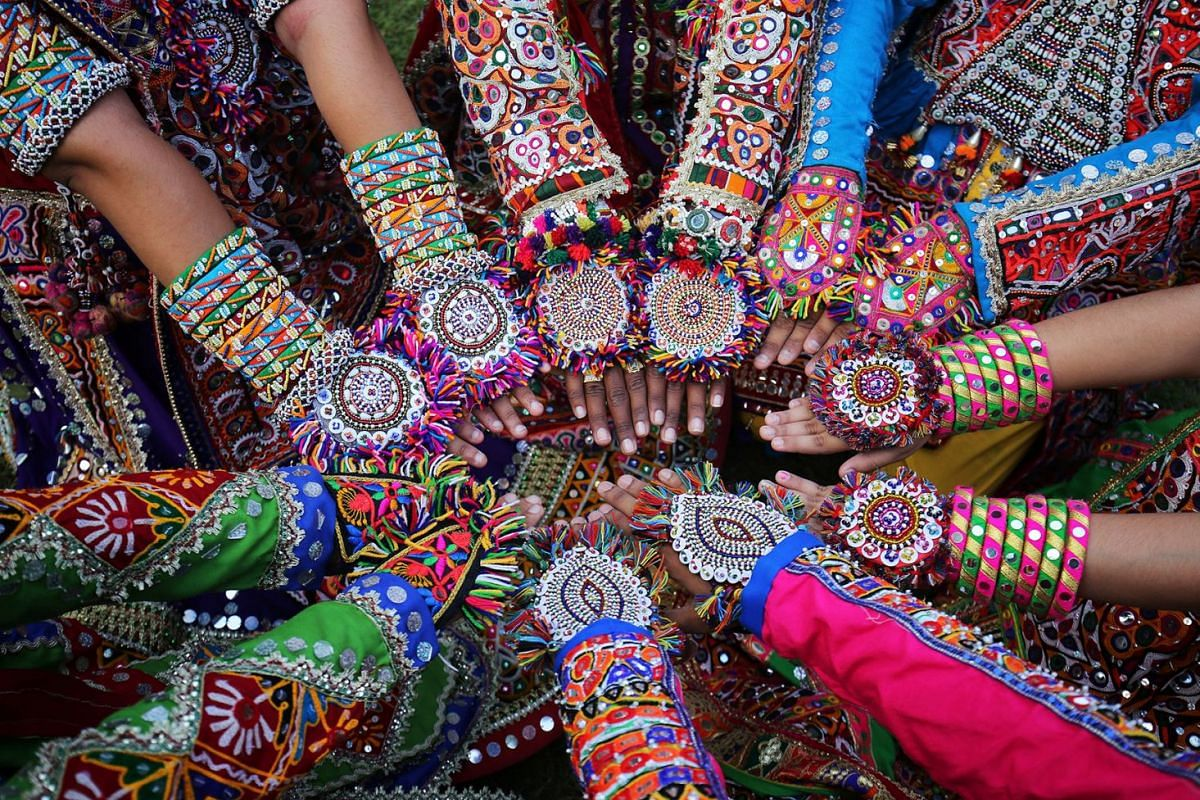 Women dressed in traditional attire display their decorated hands as they pose for pictures during rehearsals for Garba, a folk dance, ahead of Navratri, a festival during which devotees worship the Hindu goddess Durga and youths dance in traditional