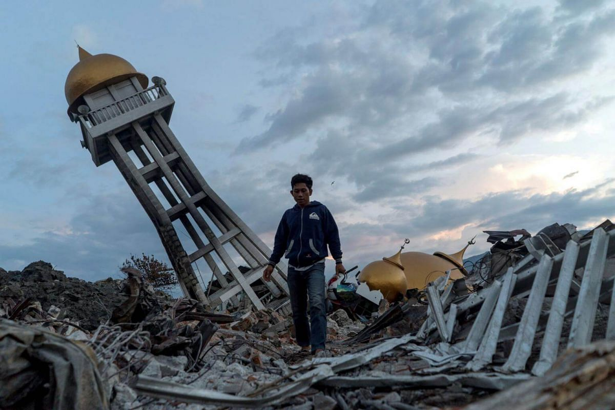 A resident walking through the debris caused by the earthquake and tsunami in Palu, on Oct 4, 2018.