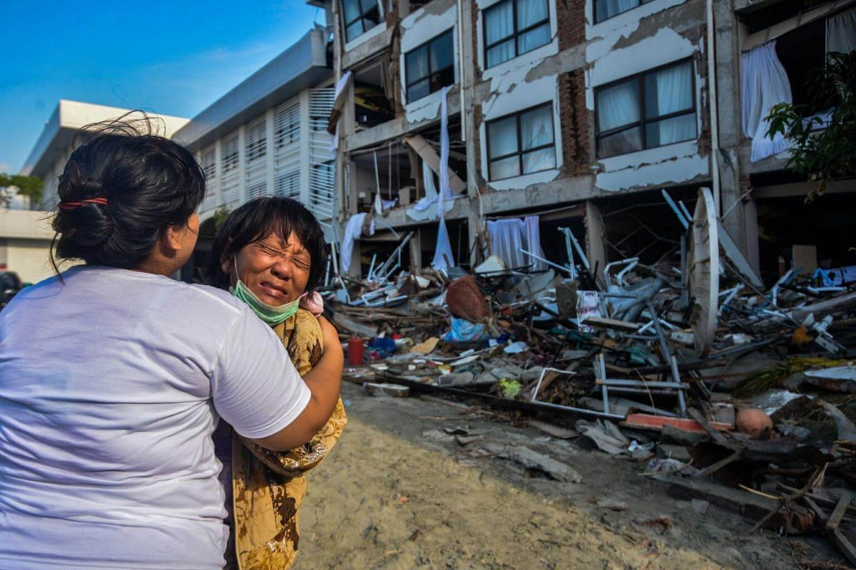 A woman mourns as rescuers search for earthquake victims inside a damaged hotel building in Palu on Oct 3, 2018.