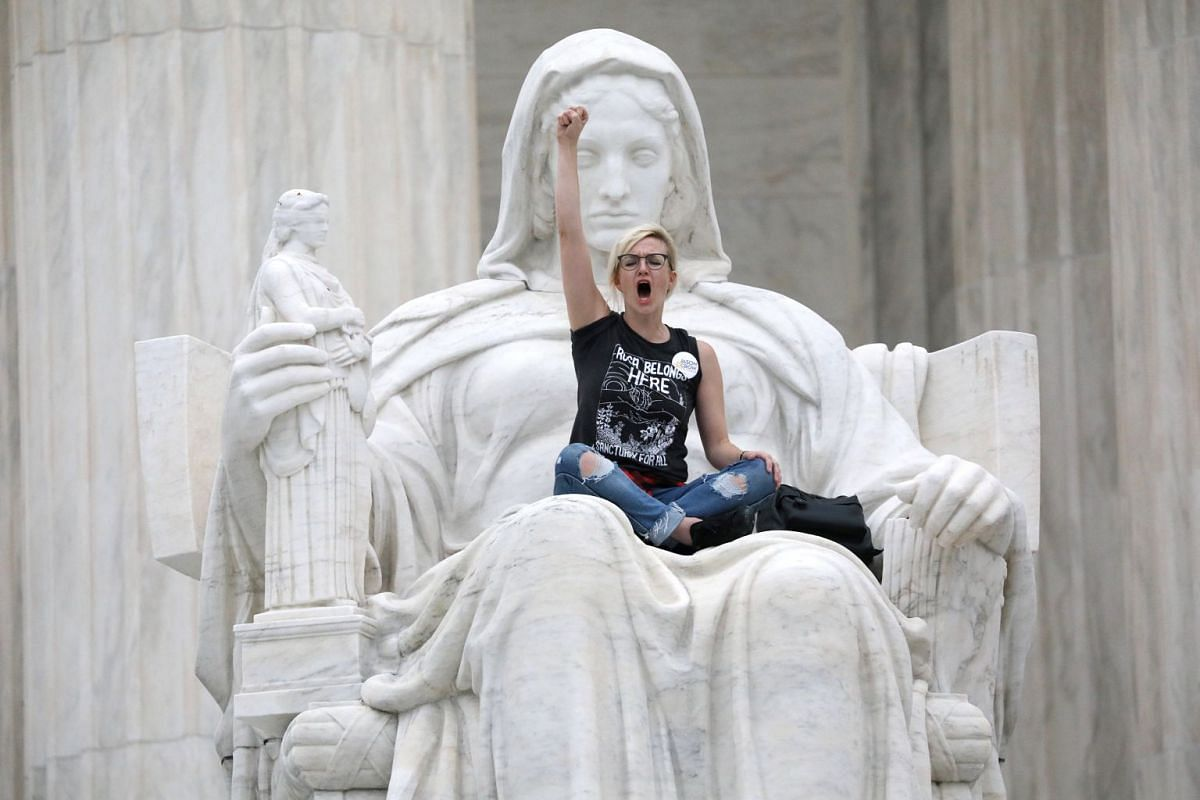 """A protester sits on the lap of """"Lady Justice"""" on the steps of the U.S. Supreme Court building as demonstrators storm the steps and doors of the Supreme Court while Judge Brett Kavanaugh is being sworn in as an Associate Justice of the court inside on"""