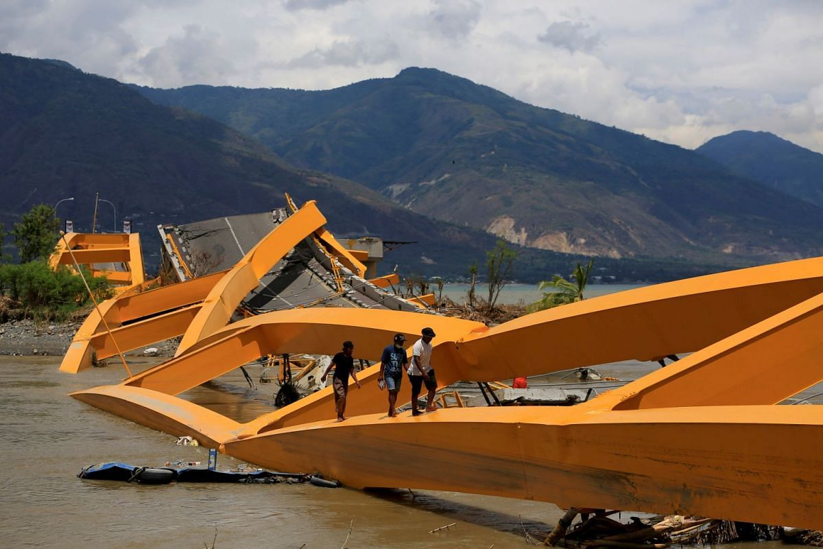 People walk on a broken bridge after it was hit by an earthquake and tsunami last week in Palu, Sulawesi island, Indonesia October 7, 2018. PHOTO: REUTERS