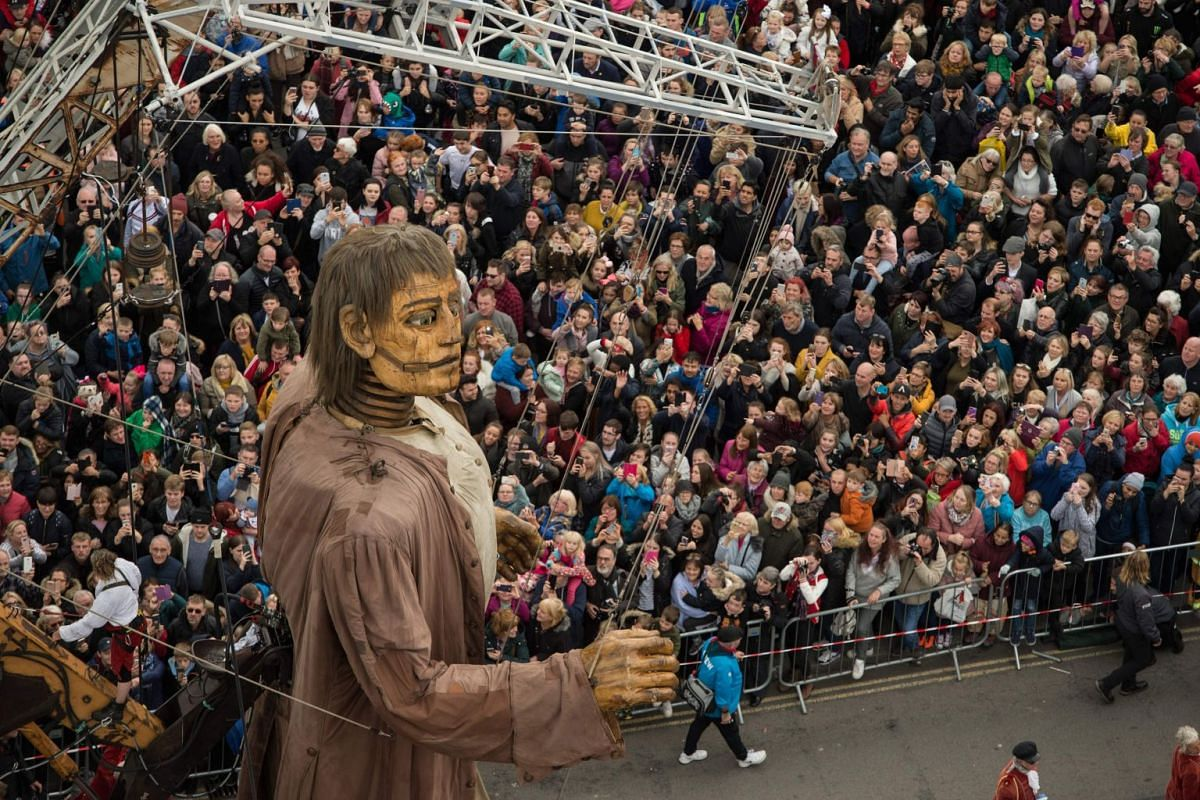 A huge puppet named Giant walks past the dockside in central Liverpool, north west England on October 7, 2018, during a production by French street theatre company Royal de Luxe entitled: Liverpool's Dream. PHOTO: AFP