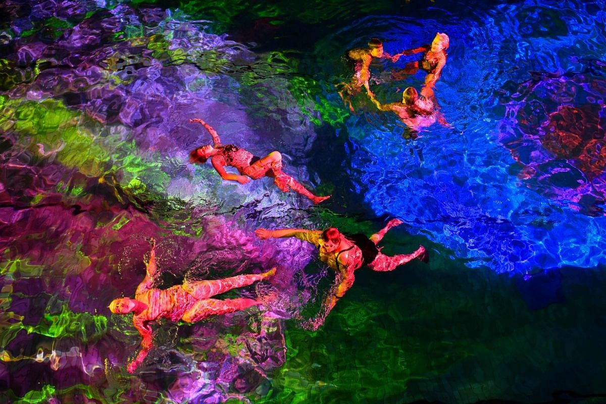 People swim in the lighted water of the Hirschengraben indoor swimming pool in Bern during an artistic performance by Swiss visual artist Pipilotti Rist and World Wide Fund for Nature (WWF) Switzerland non-governmental organization to denounce the di