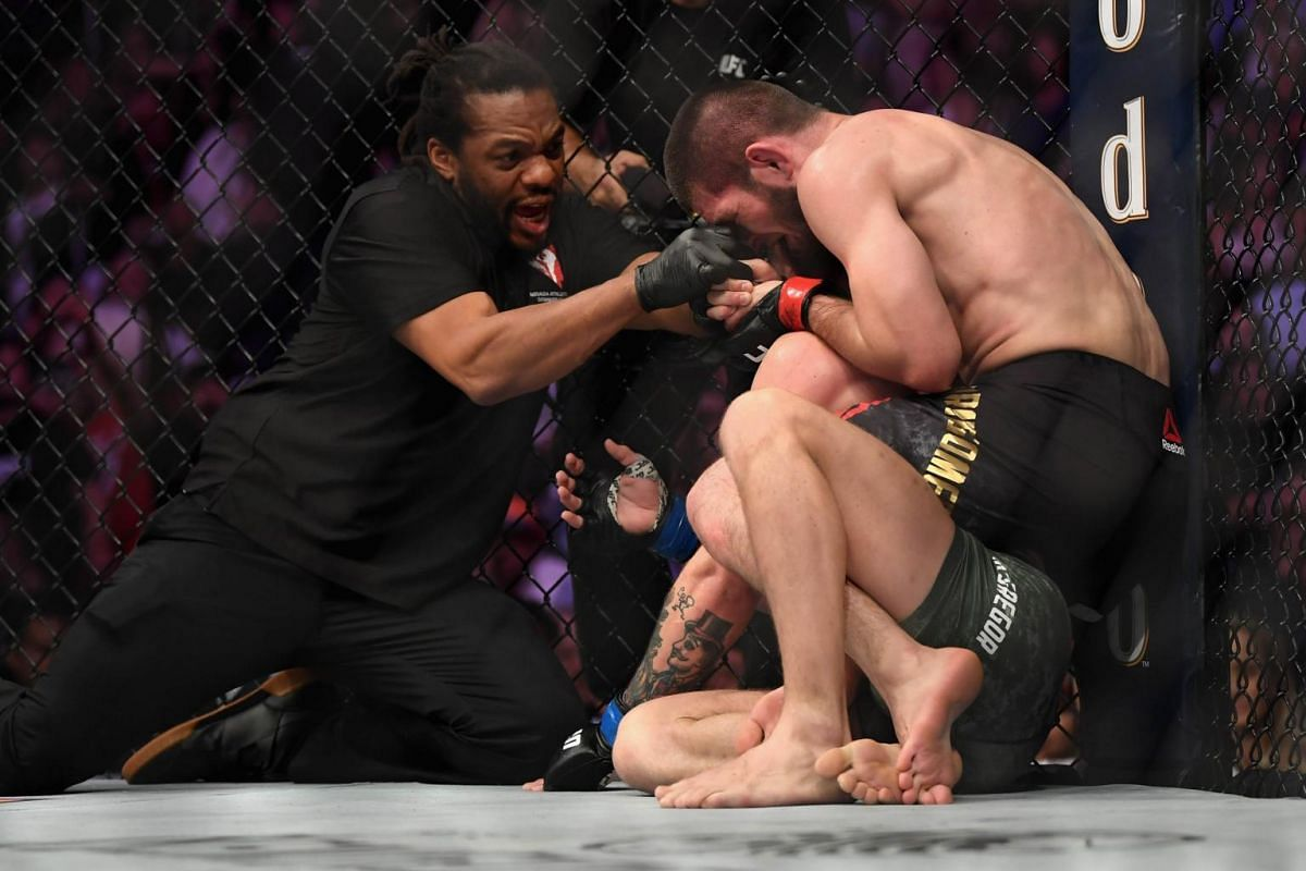 Referee Herb Dean separates Khabib Nurmagomedov (red gloves) from Conor McGregor after the latter tapped out.