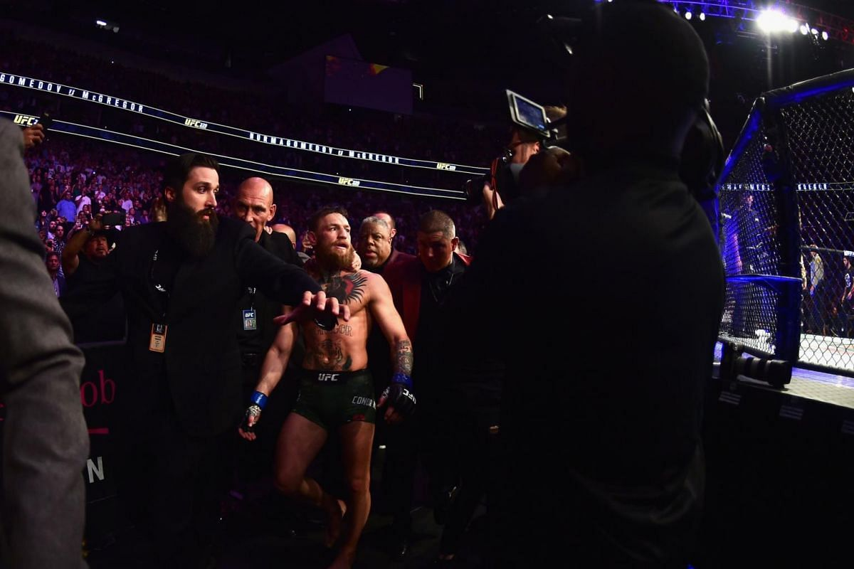 McGregor being escorted out of the octagon after his bout against Nurmagomedov.