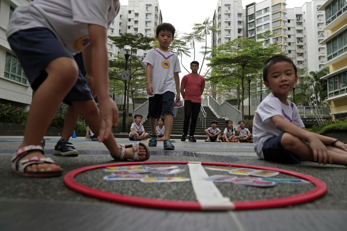 Mr Shane Lim (in red) does different kinds of sports and exercises with the pupils to build motor skills, and tries to reinforce the values of compassion, kindness and teamwork while interacting with them. Here, they are playing outdoors and learning