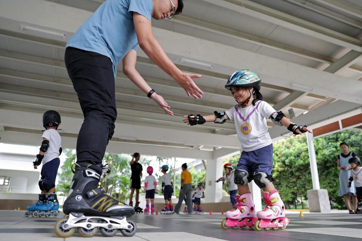 Mr Lim encourages four-year-old Gracelyn Tse as she learns to skate during an outdoor activity session in school.