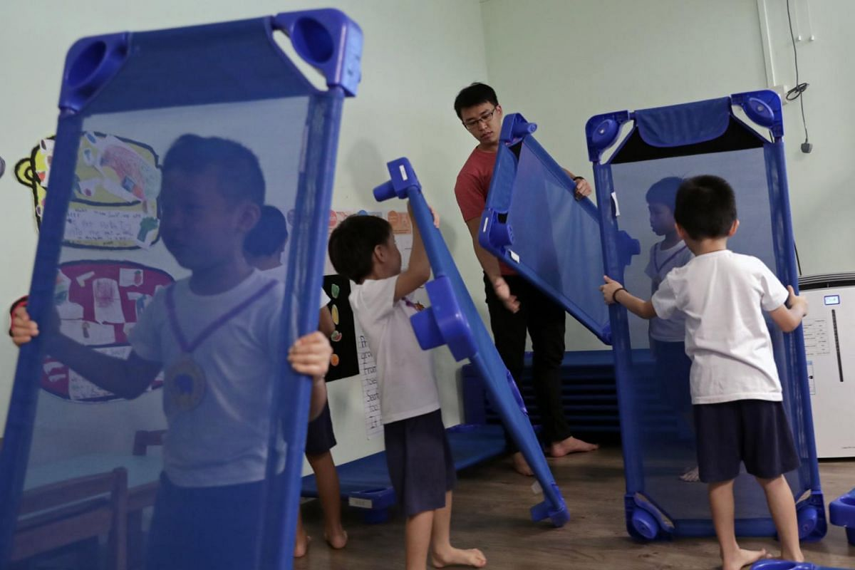 Shifting cots with the help of his pupils as they get ready for a nap.