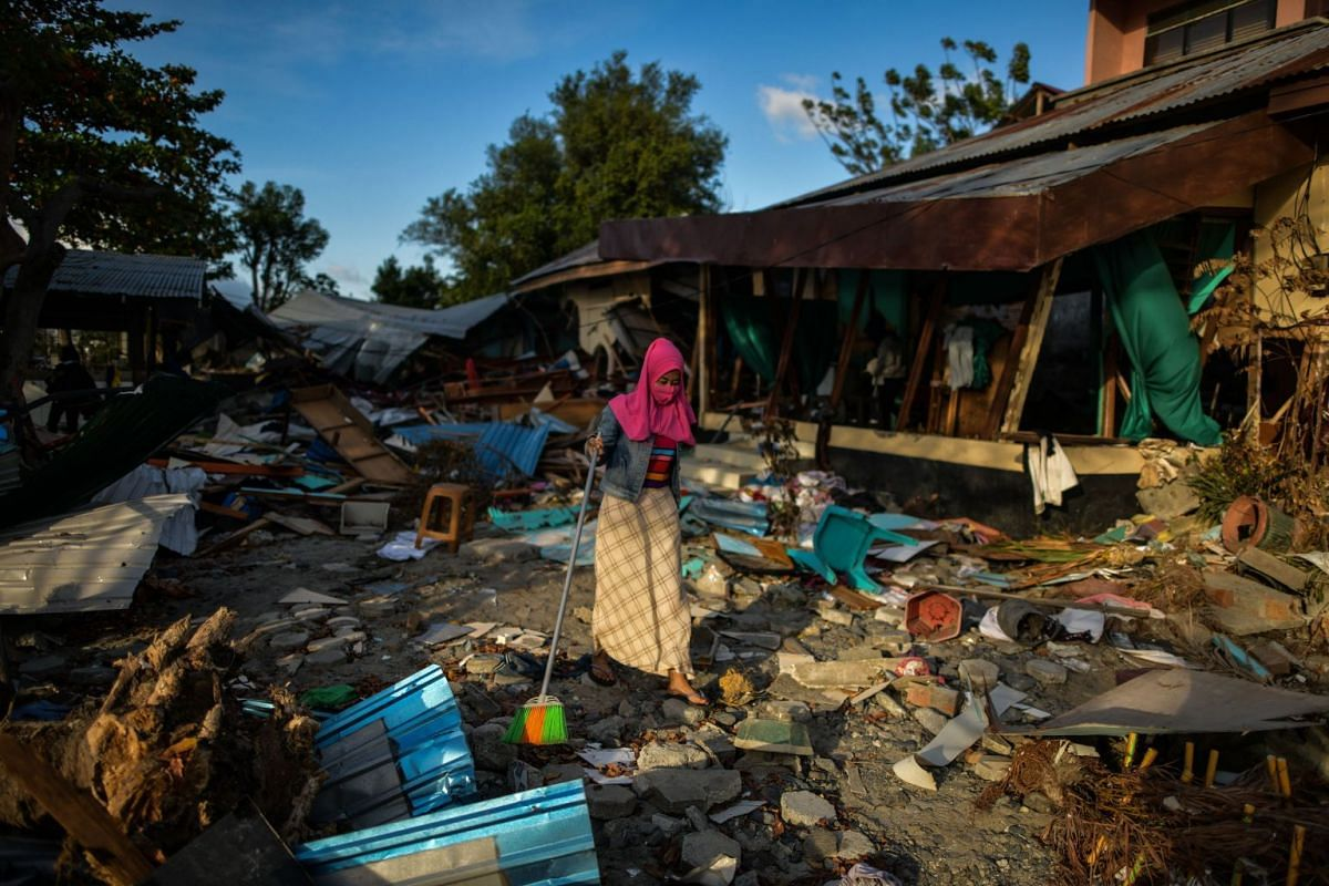 A woman clears debris from her house in Palu, Sulawesi, on Oct 8, 2018, following the Sept 28 earthquake and tsunami.