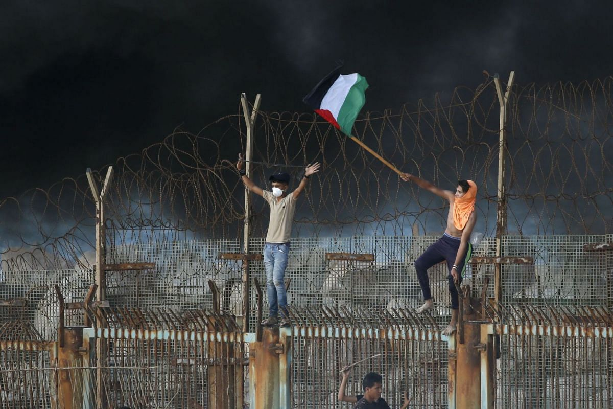 Palestinian protestors place their national flag on a metal structure during a demonstration on the beach near the maritime border with Israel, in the northern Gaza Strip, on October 8, 2018. PHOTO: AFP