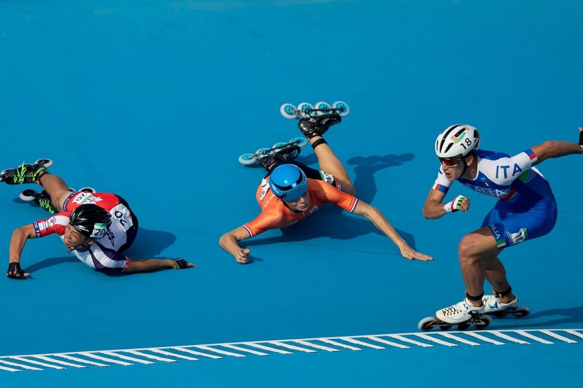 Vincenzo Maiorca of Italy takes the lead as Chiawei Chang of Taiwan and Merijn Scheperkamp of the Netherlands fall during the Roller Speed Skating Mens Combined Speed Event Final at the Paseo De La Costa during the Youth Olympic Games, Buenos Aires,
