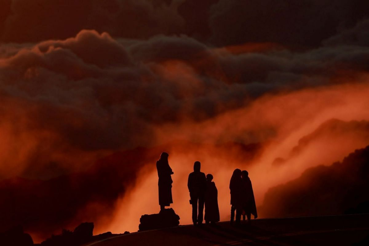 Light illuminates clouds as people watch the sunrise at Haleakea National Park in Hawaii, U.S., October 9, 2018. PHOTO: REUTERS