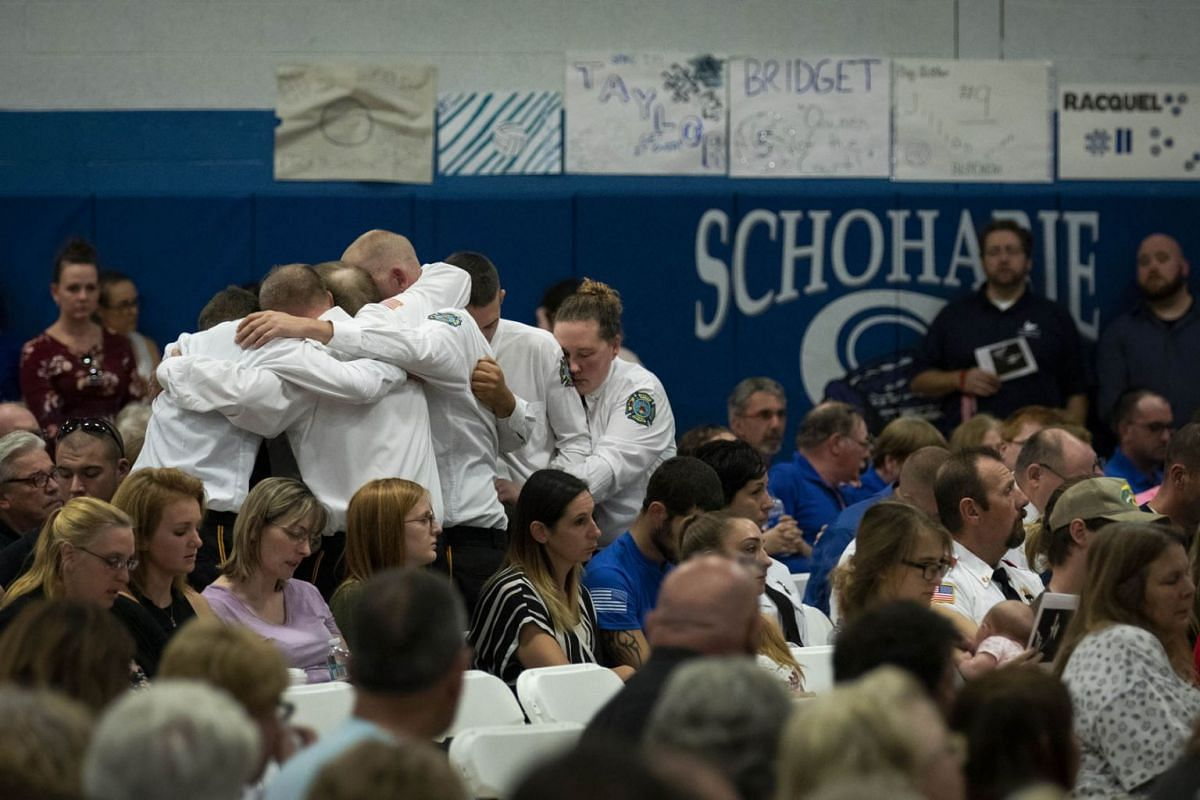 First responders embrace while the song 'Lean On Me' is played during a memorial service for the victims of a limousine crash that killed 20 people, at Schoharie County High School, October 10, 2018 in Schoharie, New York. PHOTO: GETTY IMAGES/AFP