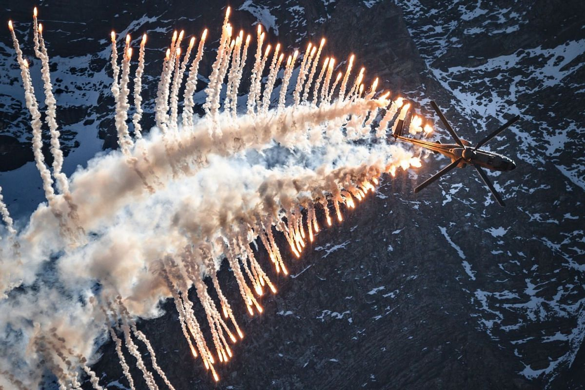 Super Puma Cougar helicopter releases flares over Brienz in the Bernese Alps on October 10, 2018, during the annual live fire event of the Swiss Air Force at the Axalp. PHOTO: AFP