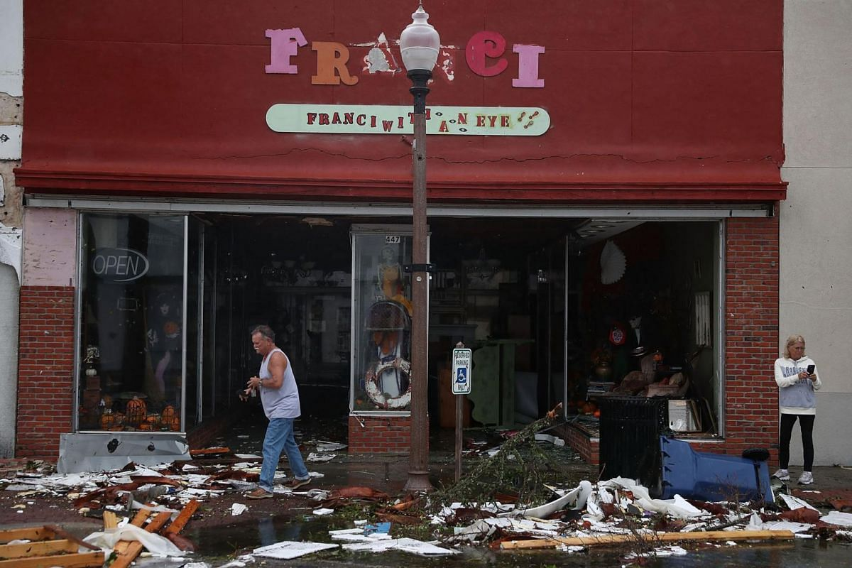 People walk past damaged stores after hurricane Michael passed through the downtown area on Oct 10, 2018.