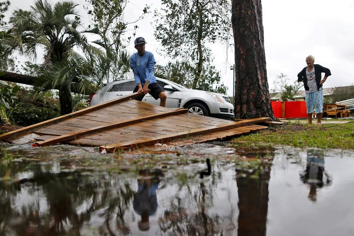 A man clears a fence damaged by Hurricane Michael at his business in Panama City Beach, Florida, on Oct 10, 2018.