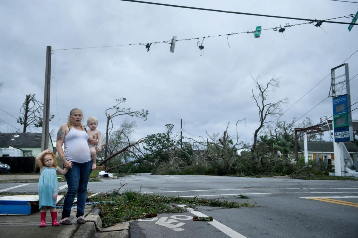 A woman and her children wait near a destroyed gas station after Hurricane Michael in Panama City, Florida, on Oct 10, 2018.