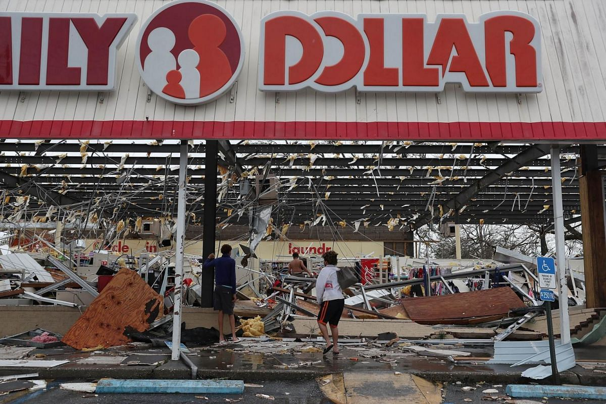 People look on at a damaged store after Hurricane Michael passed through on Oct 10, 2018.