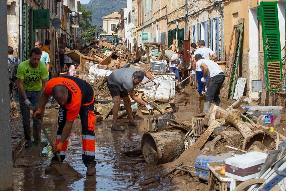 Locals clean up a street full of debris in Sant Llorenc des Cardassar on the Spanish Balearic island of Majorca on October 11, 2018. PHOTO: AFP