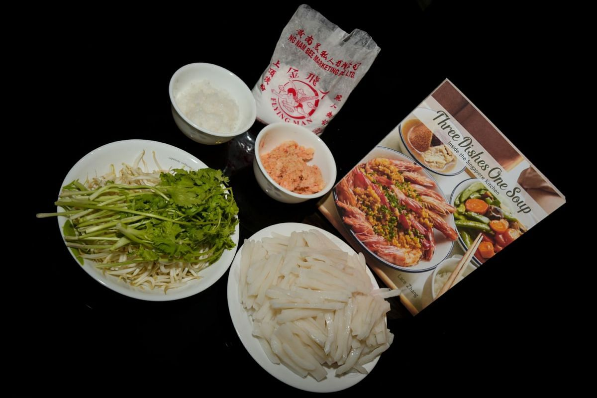(Clockwise from top left) Tapioca starch in a bowl, dried prawn with garlic and chilli, cookbook, porridge cake strips and a plate of coriander and bean sprouts.