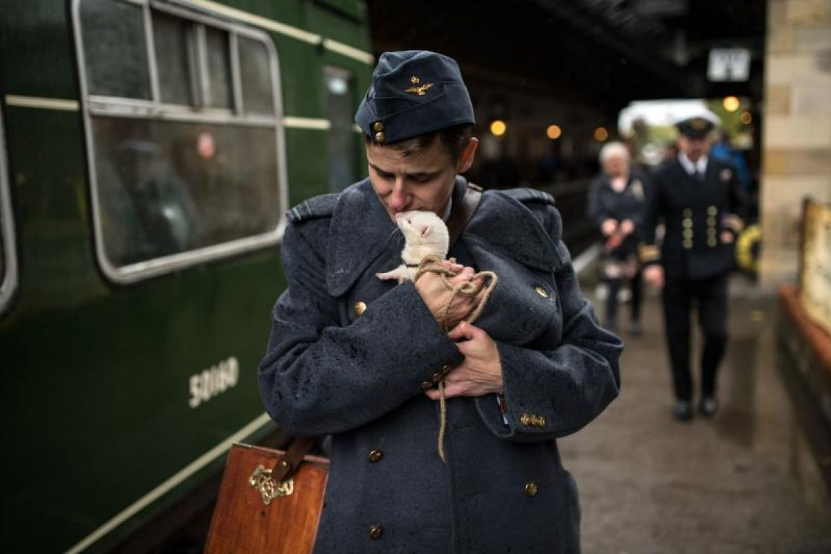 A man cuddles a ferret as they prepare to board a train during a reenactment-themed weekend, the annual 'Railway in Wartime' event held along the North Yorkshire Moors Railway, in Pickering, northern England on Oct 14, 2018. This year's focus will