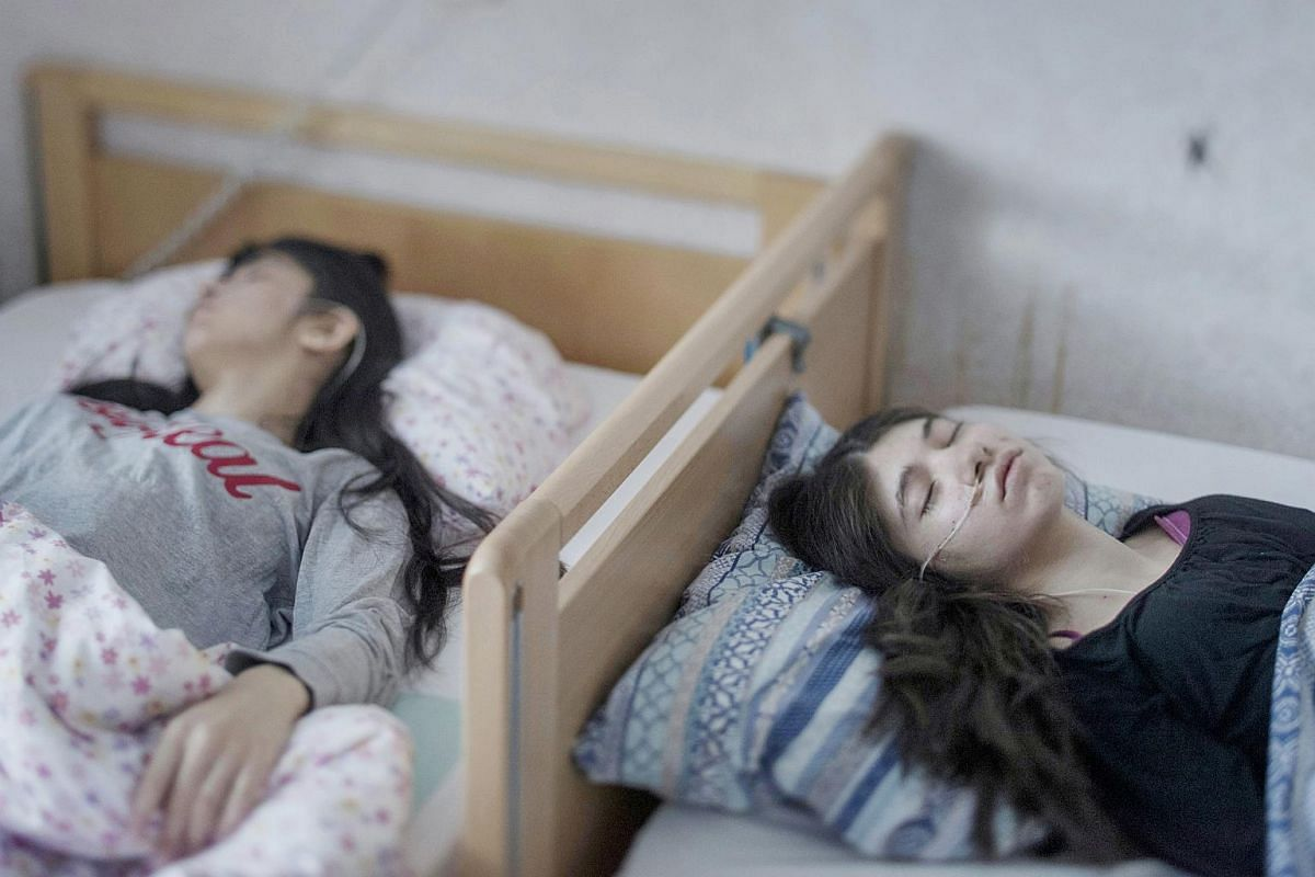Djeneta (right) has been bedridden and unresponsive for two-and-a-half years, and her sister Ibadeta for more than six months, with uppgivenhetssyndrom (resignation syndrome), in Horndal, Sweden. Djeneta and Ibadeta are Roma refugees, from Kosovo. RS