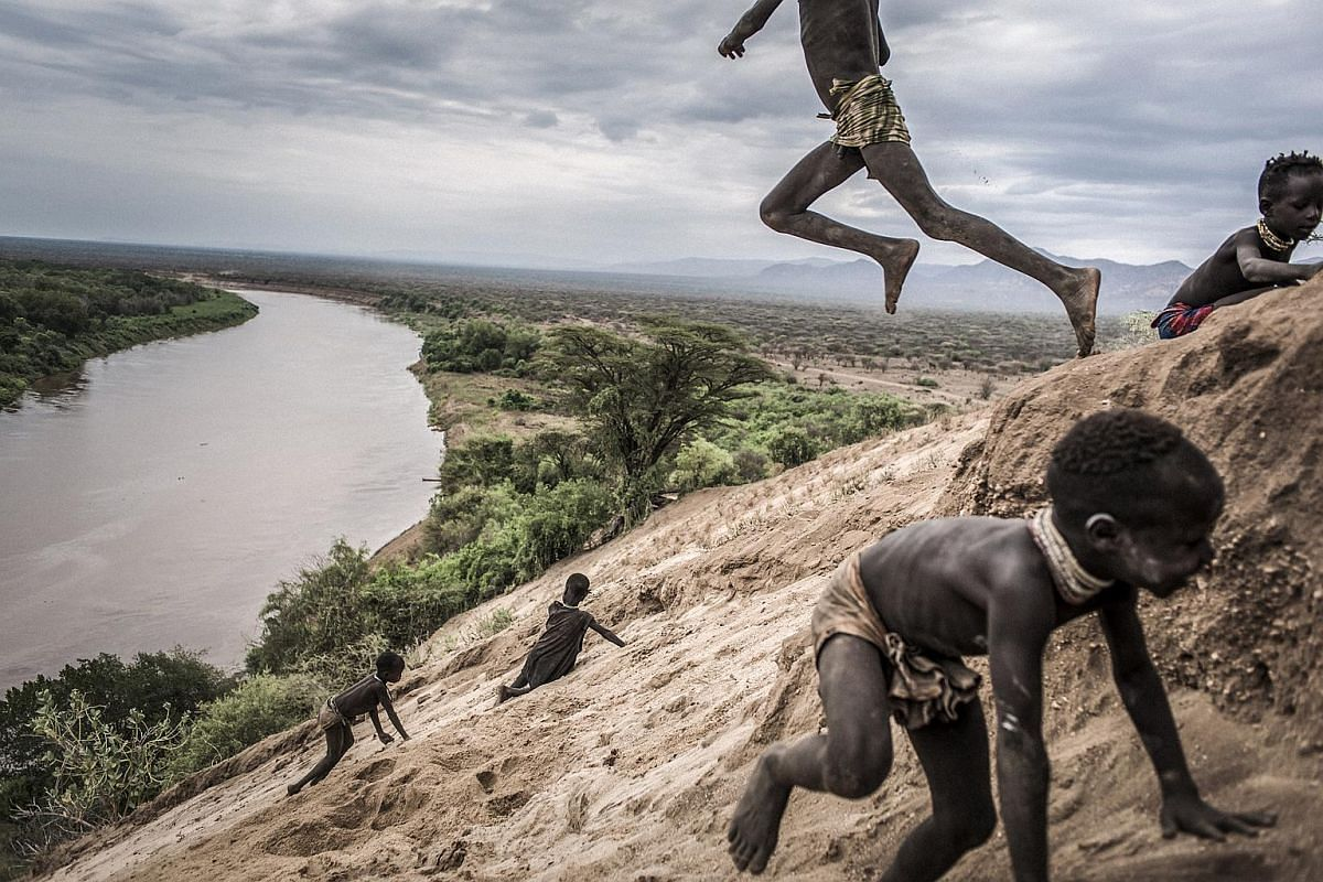 Along the oriental shore of the Omo River near the Karo village, children are playing by jumping in the sand. Karos are a small tribe with an estimated population between 1,000 and 3,000 people and lives thanks to fishing and cultivation made possibl