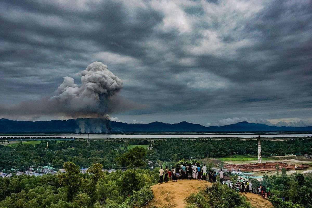 A large group of young Rohingya watch houses burn just beyond the border at Leda Makeshift Shelter in Cox's Bazaar, Bangladesh, on Sept 9, 2017.