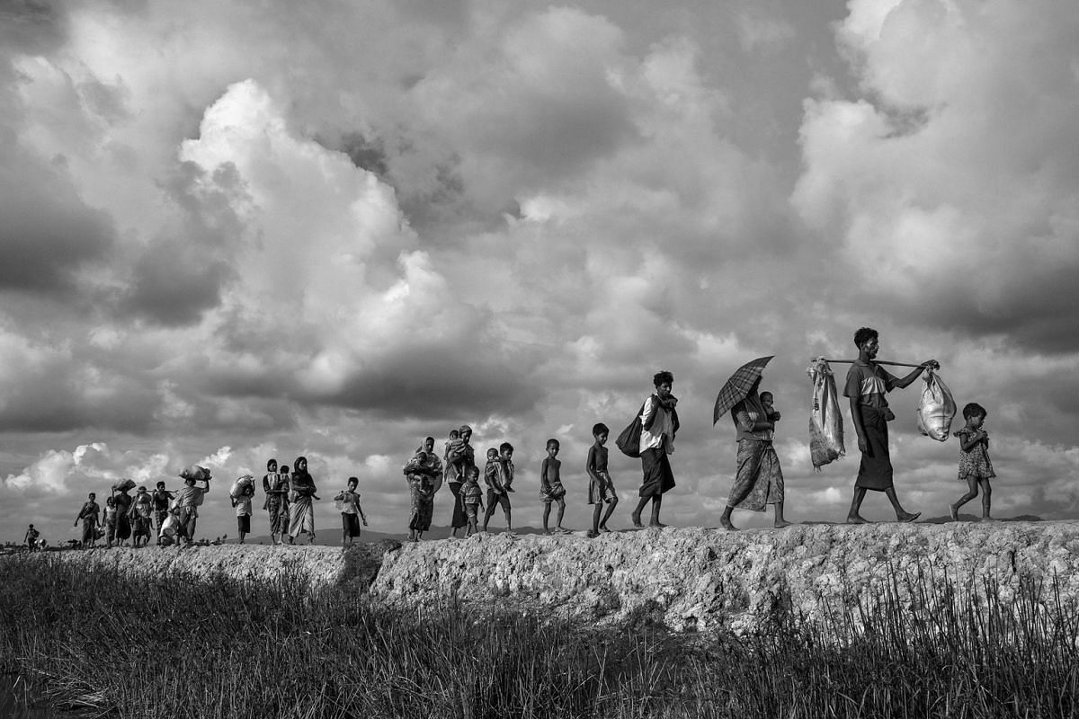 Rohingya refugees walking on the Bangladesh side of the Naf River after fleeing Myanmar, on Oct 2 last year. Attacks on the villages of Rohingya Muslims in Myanmar, and the burning of their homes, led to hundreds of thousands of refugees fleeing into