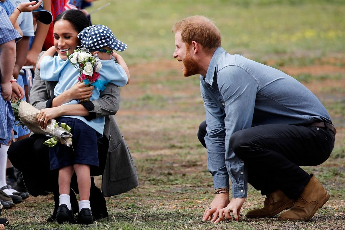 Britain's Prince Harry and Meghan, Duchess of Sussex, interact with Luke Vincent, 5, after arriving at Dubbo airport, Dubbo, Australia, on Oct 17, 2018.