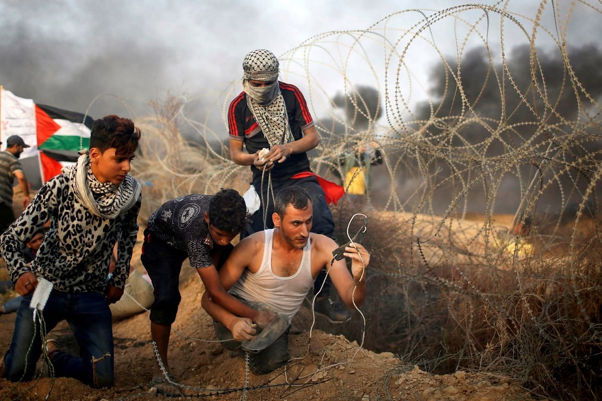 A disabled Palestinian is helped as he uses a sling to hurl stones at Israeli troops during a protest calling for lifting the Israeli blockade on Gaza and demanding the right to return to their homeland, at the Israel-Gaza border fence in Gaza Octobe
