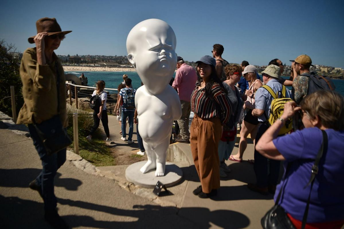 Visitors walk past a sculpture titled Niemand by Victor Fresco.