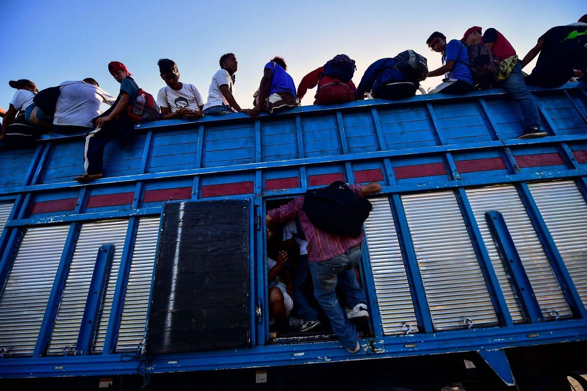 Honduran migrants heading in a caravan to the US, board a truck in Metapa on their way to Tapachula, Chiapas state, Mexico on October 22, 2018. PHOTO: AFP