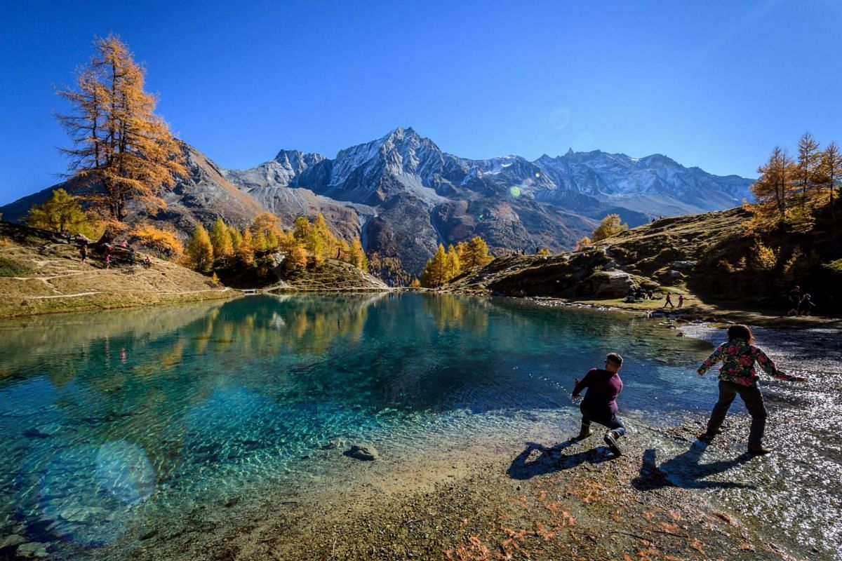 Tourists throwing stones in the Blue Lake surrounded by larch trees, above Arolla, western Switzerland, on a warm autumn day, on Oct 20, 2018.