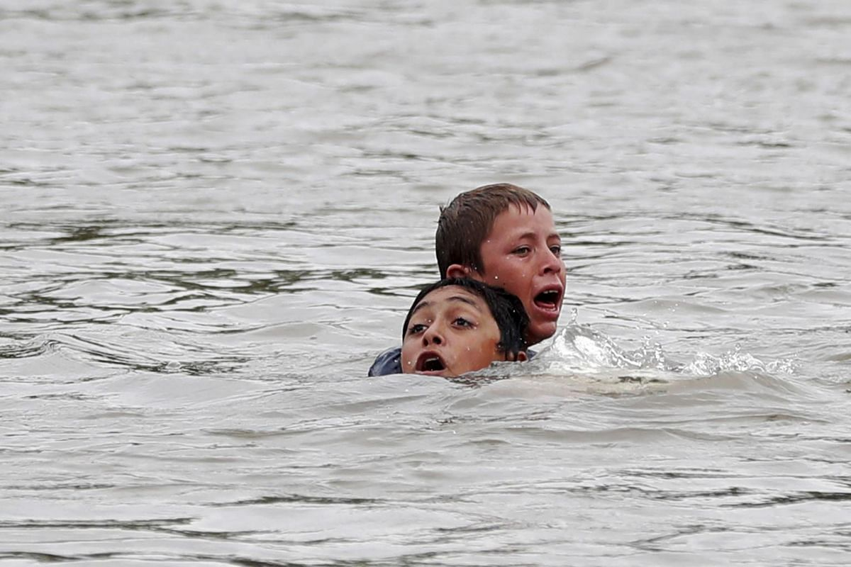 Honduran migrants cross the Suchiate River, which separates Guatemala from Mexico, on Oct 20, 2018.