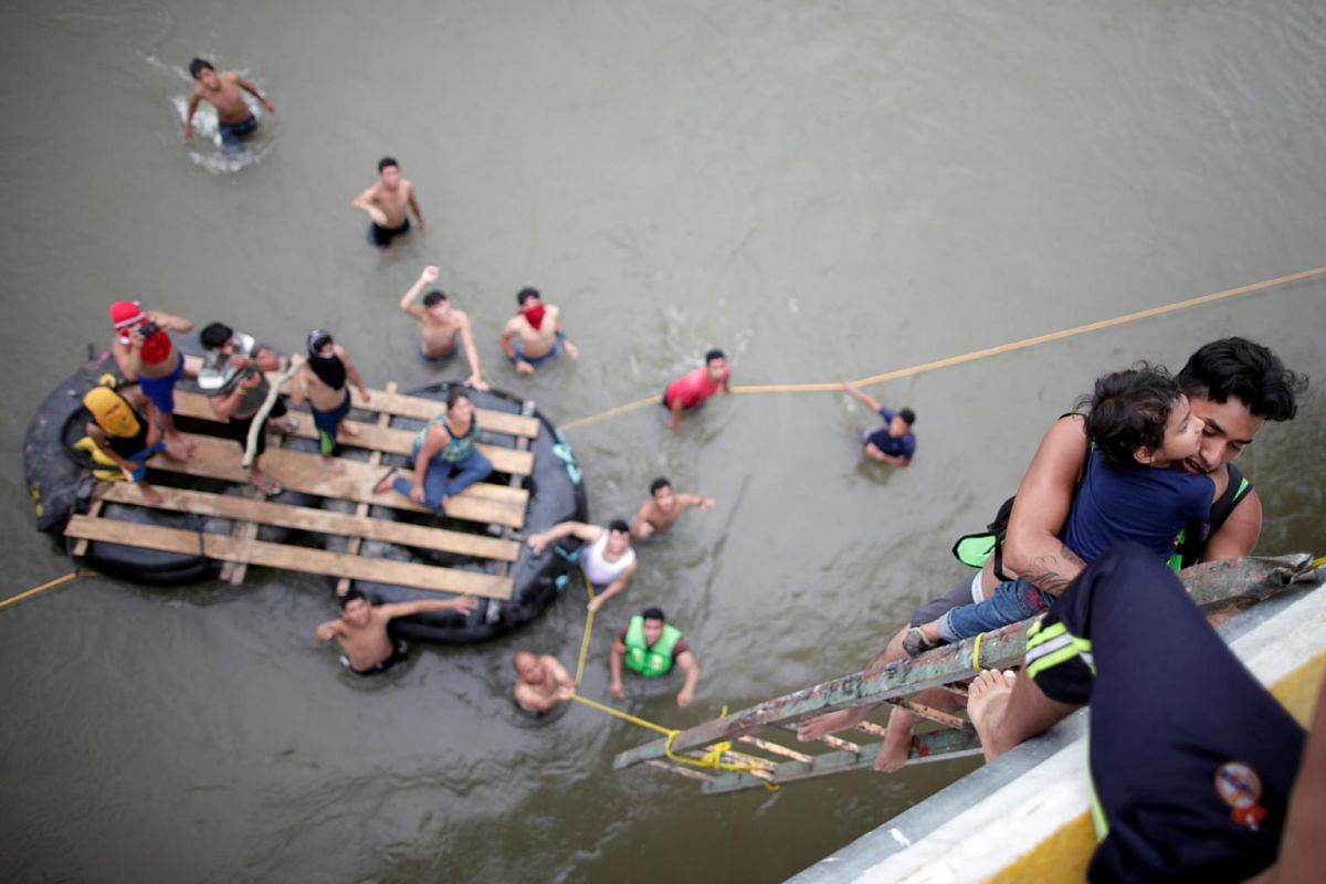 Honduran migrants use a provisional ladder to climb down from the bridge that connects Mexico and Guatemala to carry on their journey in Ciudad Hidalgo, Mexico, Oct 20, 2018.