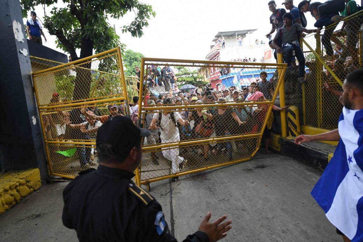 Honduran migrants tear down the gate at the Guatemala-Mexico international border bridge in Ciudad Hidalgo, Chiapas state, Mexico, on Oct 19, 2018.