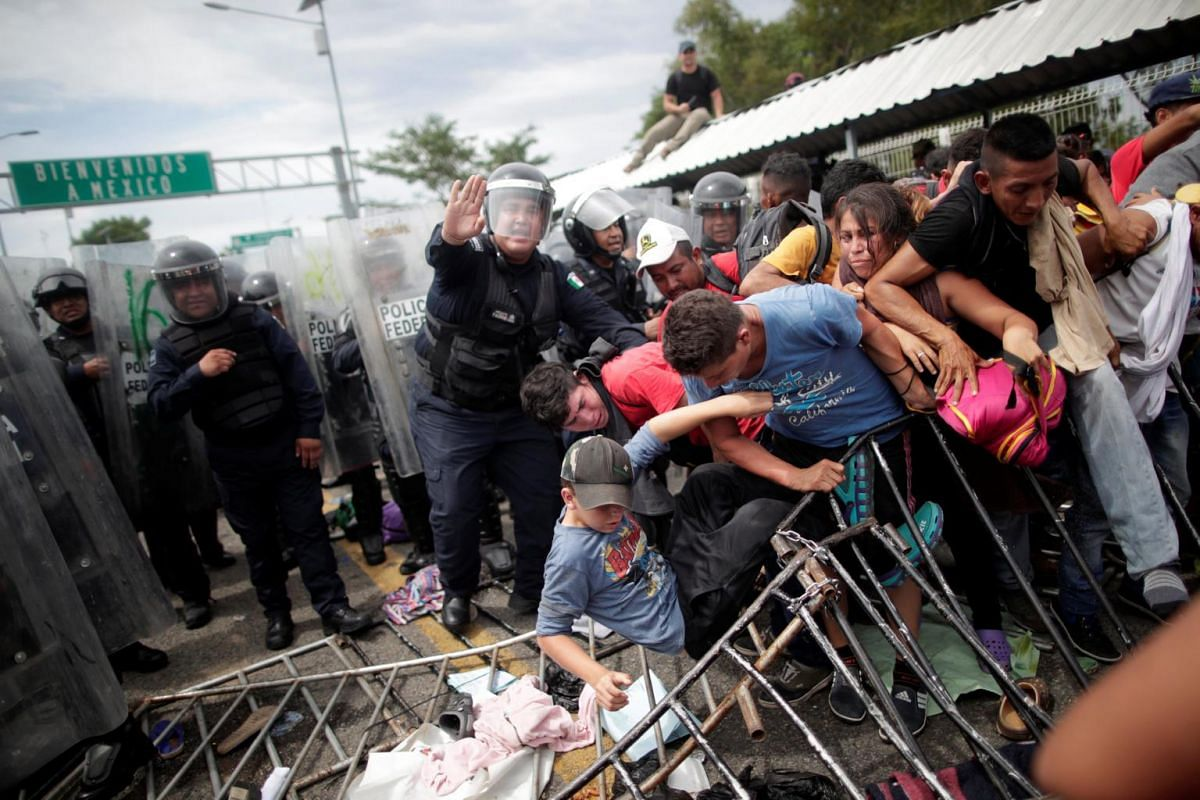 Honduran migrants push against other migrants and the police after storming the Guatemalan checkpoint to enter Mexico, in Ciudad Hidalgo, Mexico, on Oct 19, 2018.