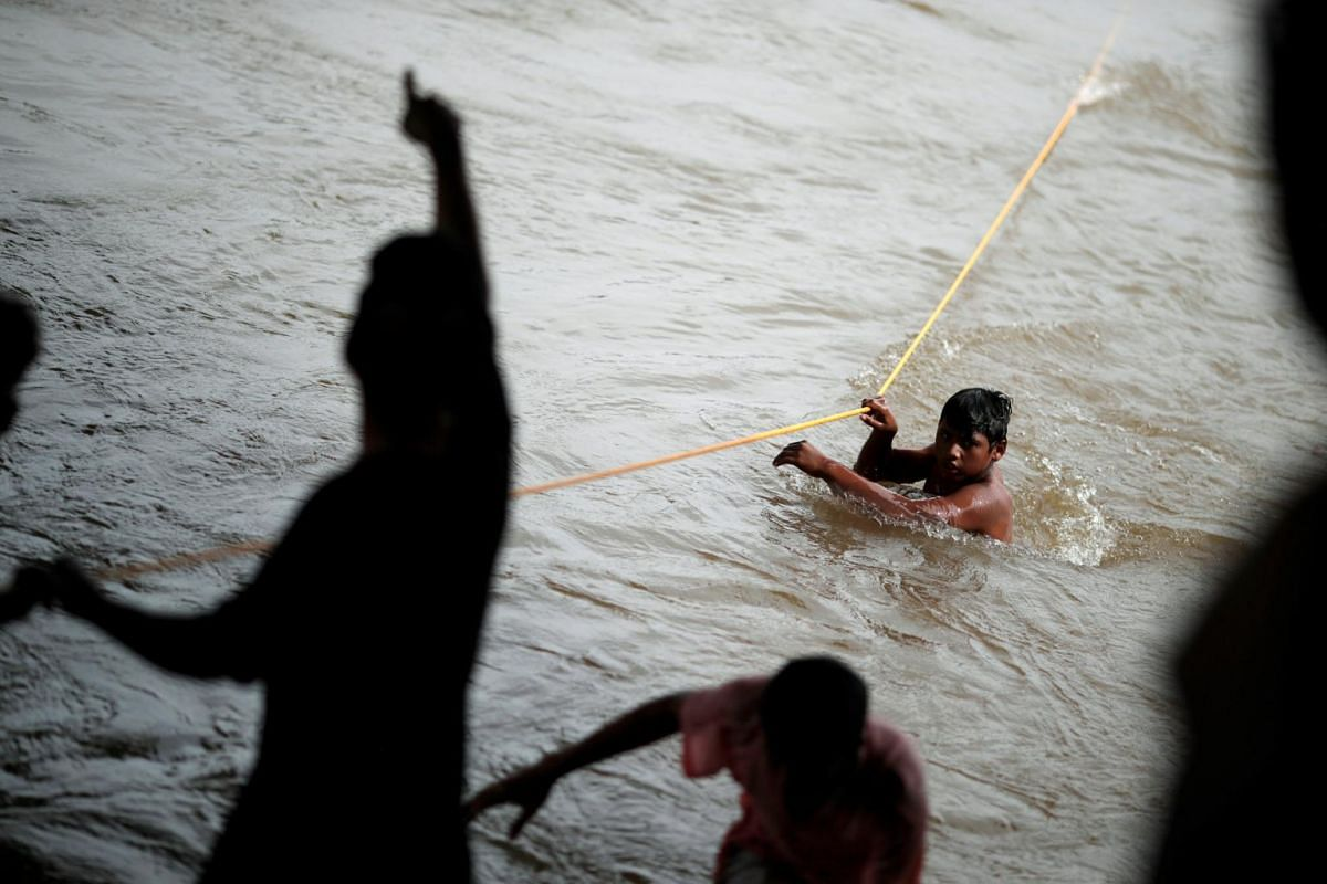 A Honduran migrant crosses the Suchiate River with the help of fellow migrants to avoid the border checkpoint in Ciudad Hidalgo, Mexico, on Oct 19, 2018.