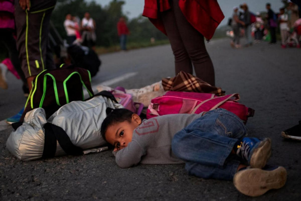 Issac, a four-year-old boy from Honduras, rests on the road on the way to Mapastepec, Chiapas state, Mexico, at dawn on Oct 24, 2018.