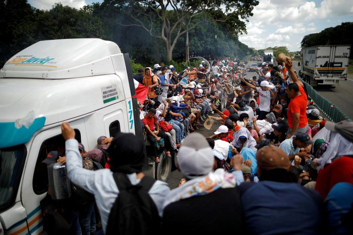 Honduran migrants hitchhike on a truck along the highway as they continue their journey in Tapachula, Mexico, on Oct 22, 2018.