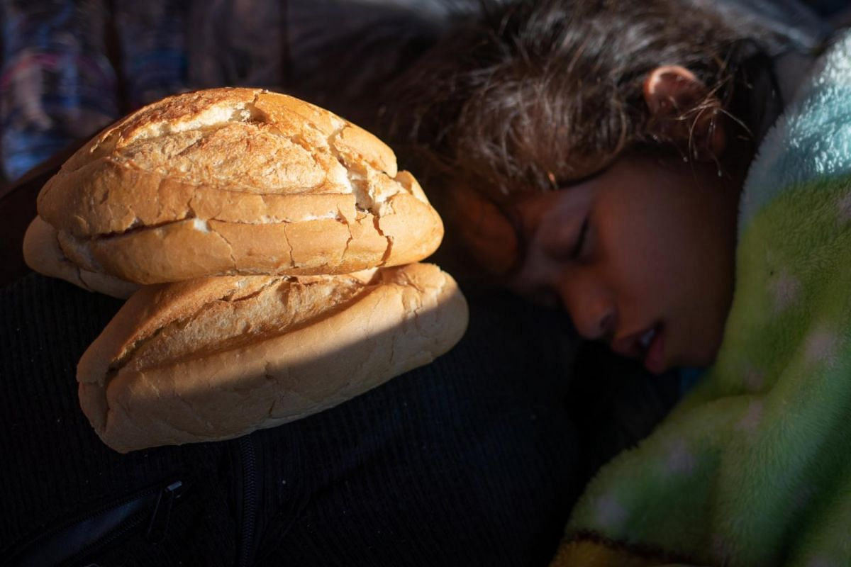 A girl sleeps next to bread donated by a passer-by in Tapachula, Mexico, on Oct 22, 2018.