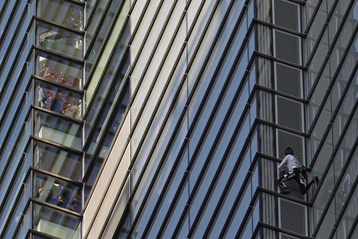 """People look out of windows as French urban climber Alain Robert, also known as """"Spider-Man"""", climbs Heron Tower, 110 Bishopsgate, in central London, on Oct 25, 2018."""