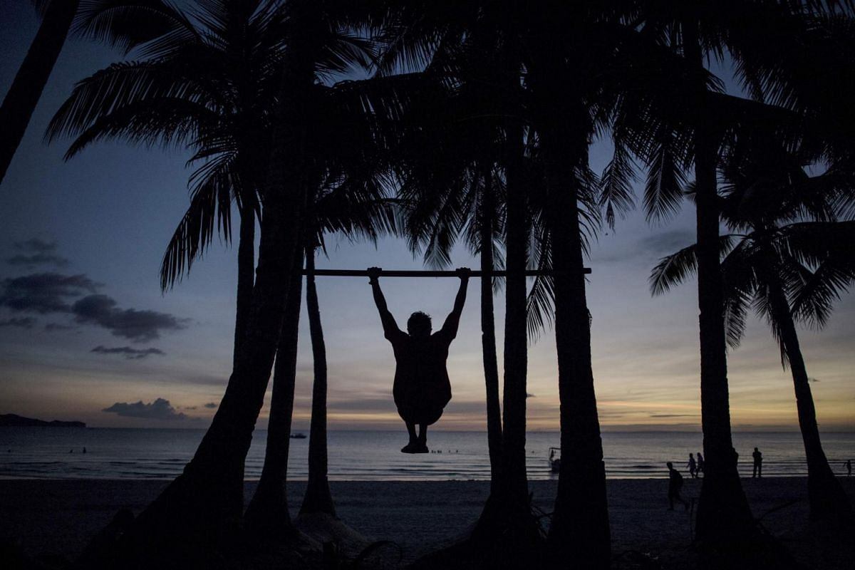 A man does pull-ups at a beach on the Philippine island of Boracay, on Oct 25, 2018.